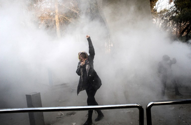 An Iranian woman raises her fist amid the smoke of tear gas at the University of Tehran during a protest driven by anger over economic problems, in the capital Tehran on December 30, 2017. Students protested in a third day of demonstrations sparked by anger over Iran's economic problems, videos on social media showed, but were outnumbered by counter-demonstrators. / AFP PHOTO / STR